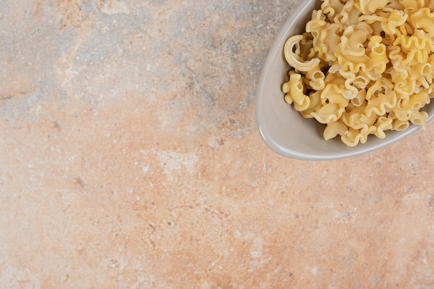 Een grijze kom onvoorbereide macaroni op marmeren ruimte.