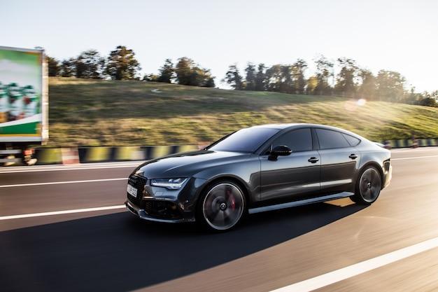 Een grijze luxe sedan auto rijden op de snelweg.