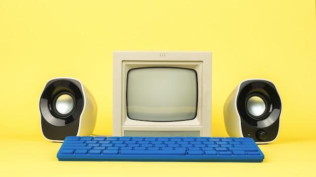 Een grijze monitor met stijlvolle luidsprekers en een blauw toetsenbord op een gele achtergrond. stijlvolle vintage apparatuur.