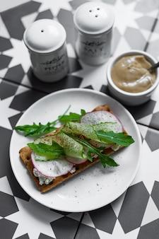 Een grijze plaat met een broodje met buko kaas, radijs en oruguts op een kleurrijke grafische tafel (aziatische, zuidelijke stijl). een gezond ontbijt met groenten en kruiden. lekker hapje