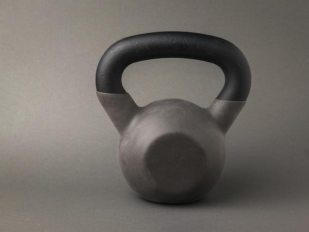Een grijze sportkettlebell op een donkergrijze achtergrond. sportieve levensstijl.