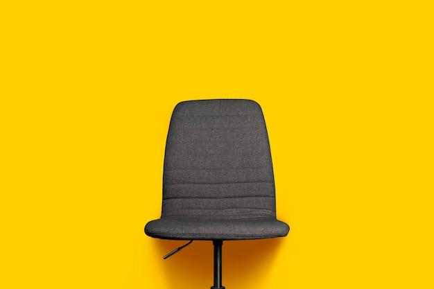Een grijze stoffen bureaustoel op geel