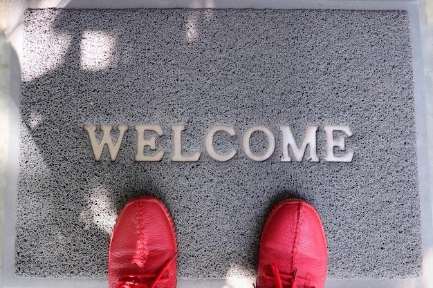 Een grijze welkomstdeurmat met voeten die rode schoenen dragen