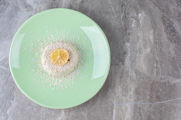 Een groen bord met heerlijk eten en een schijfje verse citroen.