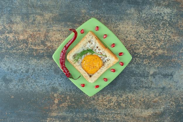 Een groen bord vol omelet in wit brood met peper
