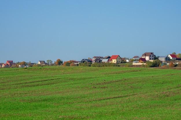 Een groen lenteveld voor een modern dorp op een heuvel tegen een helderblauwe lucht. landbouwgrond. rusland.