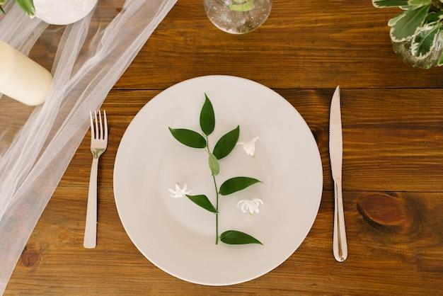 Een groen takje met bladeren op een serveerschaal op de feesttafel. decoratie voor bruiloft of verjaardag