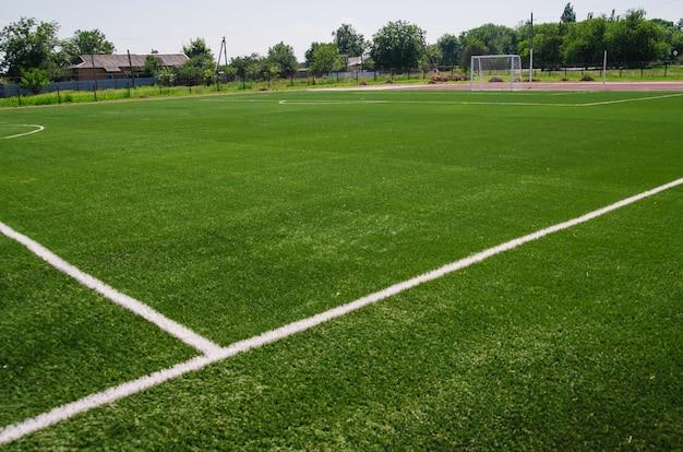 Een groen voetbalveld. een kunstgrasveld in een school of openbaar park. sportveld voor kinderen en volwassenen.