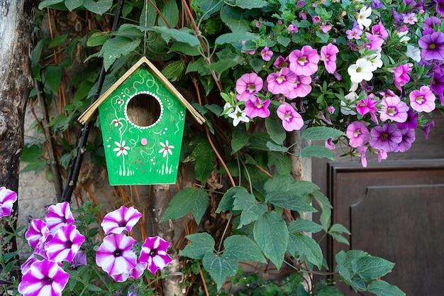 Een groen vogelhuisje hangt aan een boom omringd door petuniabloemen.