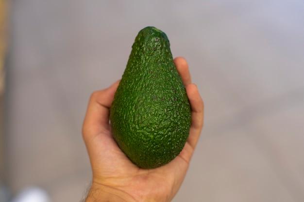 Een groene avocado in de hand van een persoon