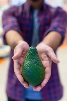 Een groene avocado in handen van een verkoper