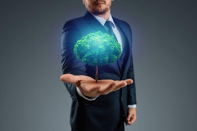 Een groene boom groeit uit de hand van een man.