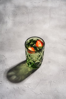 Een groene geometrische glazen beker met zoet water en aardbeien fruit met kleurrijke schaduw lichtstralen op stenen betonnen oppervlak
