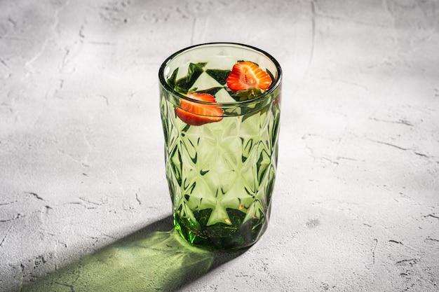 Een groene geometrische glazen beker met zoet water en aardbeien fruit