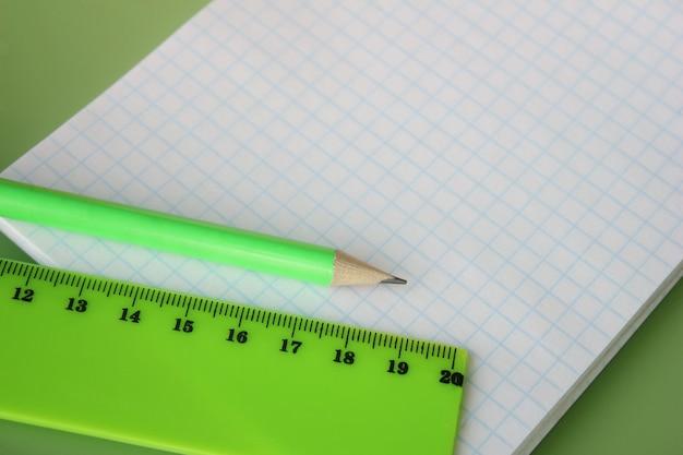Een groene liniaal en een potlood bevinden zich op het notebook. kopieer ruimte.