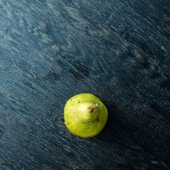 Een groene peer op een donkere ondergrond