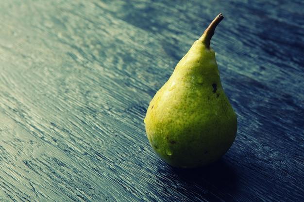 Een groene peer op een donkere tafel