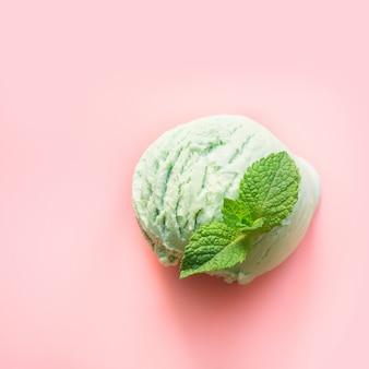 Een groene pistache of matcha thee ijs bal met munt op roze achtergrond
