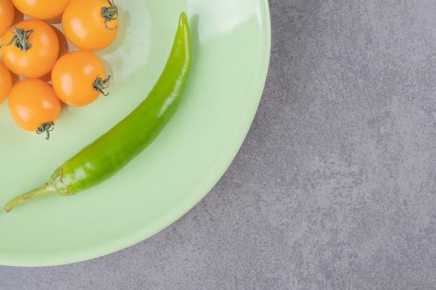 Een groene plaat met gele kersentomaten en spaanse peperpeper.