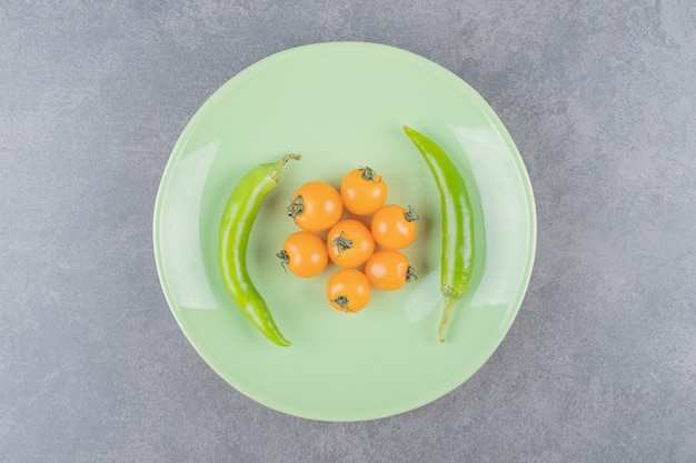 Een groene plaat met gele kersentomaten en spaanse peperpeper