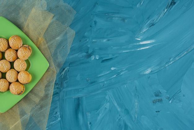Een groene plaat met gelei gummy hamburgers op een blauwe achtergrond.