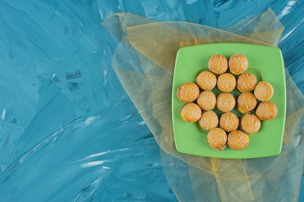 Een groene plaat met gelei gummy hamburgers op een blauwe ondergrond