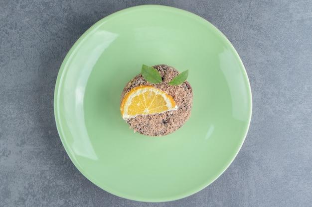 Een groene plaat met koekje en schijfje citroen
