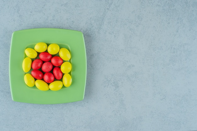 Een groene plaat met zoete gele en rode snoepjes op een witte ondergrond