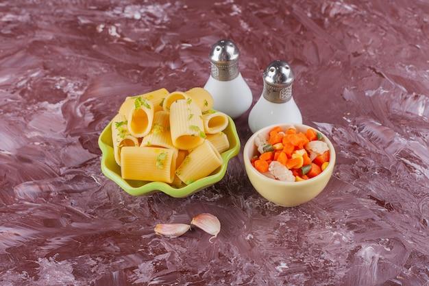 Een groene plaat van droge ruwe deegwaren met verse gemengde groentesalade en kruiden.