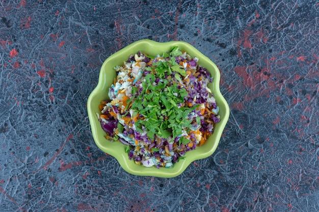 Een groene plaat van groentesalade met kruiden.