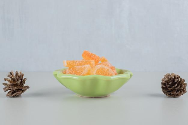 Een groene plaat van oranje suikergeleisuikergoed met dennenappels.