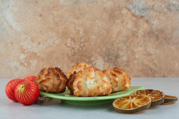 Een groene plaat van ronde zoete koekjes met gedroogde sinaasappelen en kerstballen.