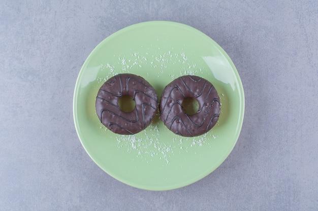 Een groene plaat van twee verse chocolade donuts met suikerpoeder.