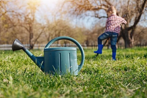 Een groene plastic gietende pot die zich op tuingras bevindt met een kind dat groentepleisters op de achtergrond graaft