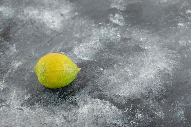 Een groene rijpe citroen op een marmeren ondergrond.