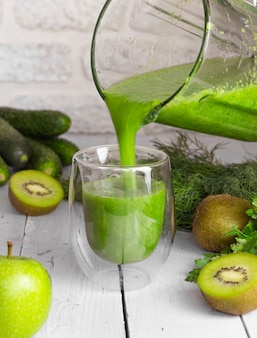 Een groene smoothie wordt uit een blender in een glas op een lichte achtergrond gegoten. gezond eten koken. kiwi, appels, komkommers en groenen.