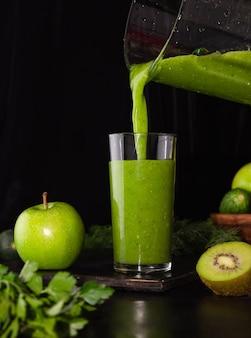 Een groene smoothie wordt uit een blender in een glazen glas op een zwarte achtergrond gegoten. gezond eten koken. kiwi, appels, komkommers en groenen.