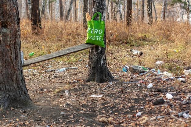 Een groene textielzak met het opschrift nul afval staat in het bos naast het afval dat op de grond is verspreid. veel plastic borden en flessen alcohol. selectieve aandacht.