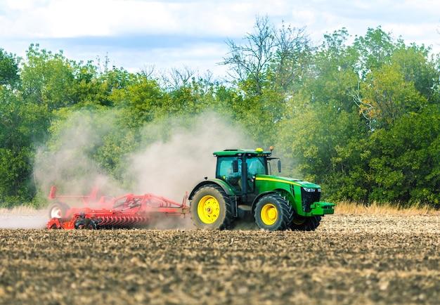 Een groene tractor werkt in het veld. grondbewerking. landbouw werk.