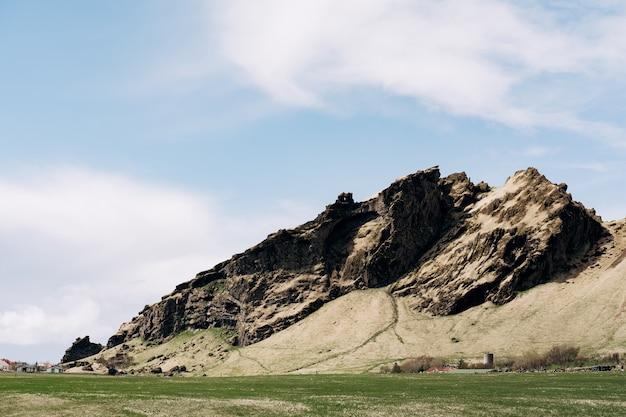 Een groene weide een veld voor grazend vee met gras tegen de achtergrond van rotsachtige bergen en