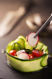 Een groentesnack gemaakt van verse groenten zoals komkommer, tomaat, fetakaas en microgreens. chef-kok versiert een gastronomisch gerecht met radijs met een pincet. macro, selectieve focus, voedsel plateren