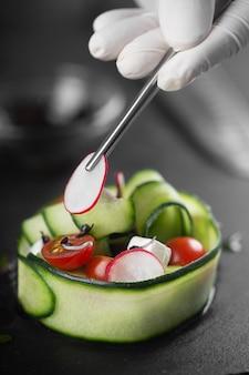 Een groentesnack gemaakt van verse groenten zoals komkommer, tomaat, fetakaas en microgreens. chef-kok versiert een gastronomisch gerecht met radijs met een pincet