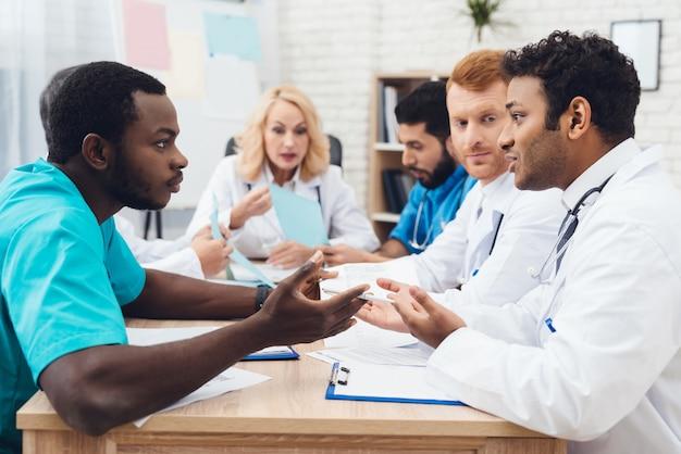 Een groep artsen van verschillende rassen maakt ruzie.