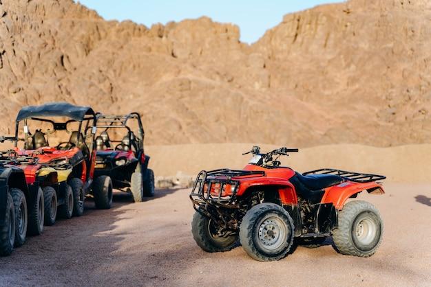 Een groep atv's en motoren staat klaar om op woestijnavontuur te gaan.