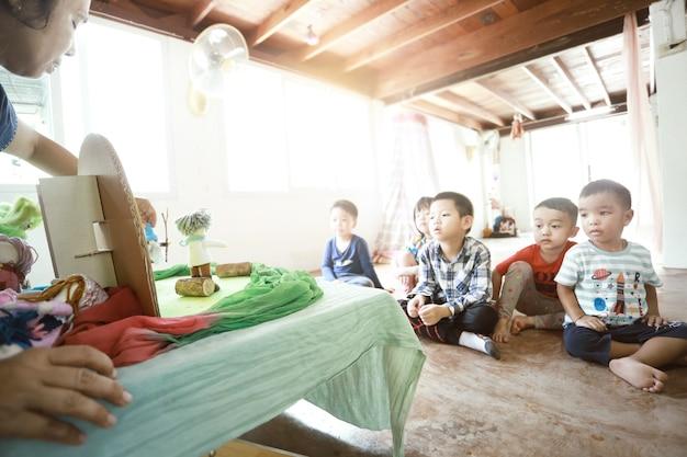 Een groep aziatische kinderen zit en luistert naar de leraar die een verhaal vertelt met handgemaakte waldorf-poppen.