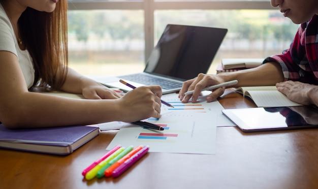 Een groep aziatische studenten zit en maakt huiswerk en rapporteert in de bibliotheek.