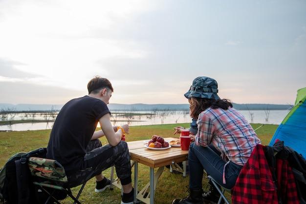 Een groep aziatische vrienden die koffie drinken en tijd doorbrengen met een picknick in de zomervakantie. ze zijn blij en hebben plezier op vakantie.