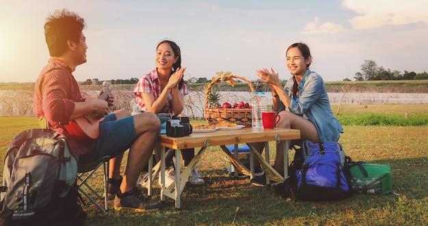 Een groep aziatische vrienden die ukelele spelen en tijd doorbrengen met een picknick in de zomervakantie. ze zijn gelukkig en hebben plezier op vakantie.