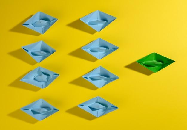 Een groep blauwe papieren boten en een groene led op een geel oppervlak. het concept van een sterke leider, manipulatie van de massa, een hecht team en effectief management