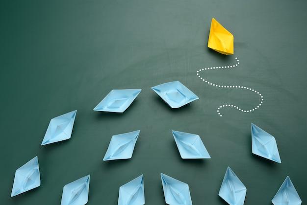 Een groep blauwe papieren boten vaart in de ene richting, een gele vaart in de tegenovergestelde richting. het concept van een buitengewone persoonlijkheid, handelen in strijd met de fundamenten van de samenleving